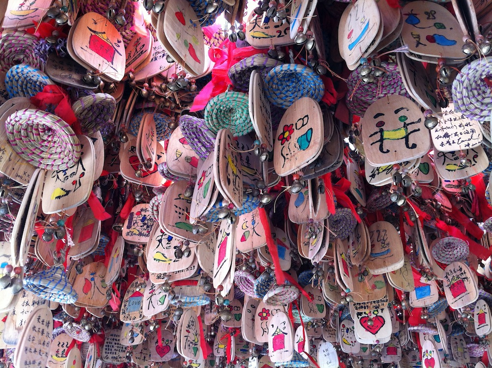 "Tourists' wishes, on kitschy wooden ""Bunong bells"""