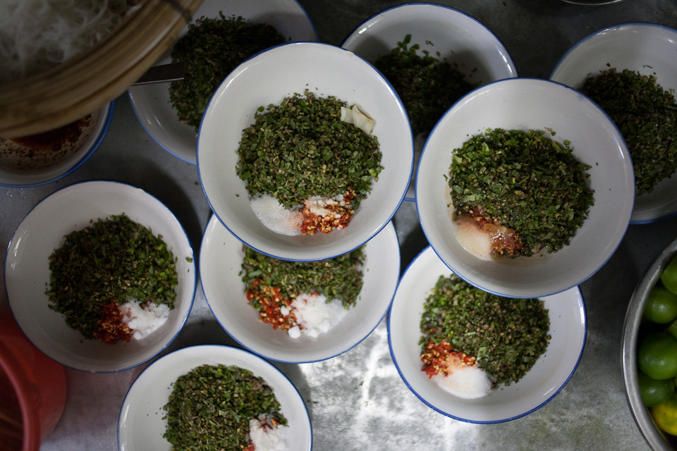 Bowls of herbs, chile, and salt, pre-prepared for noodle dipping sauce
