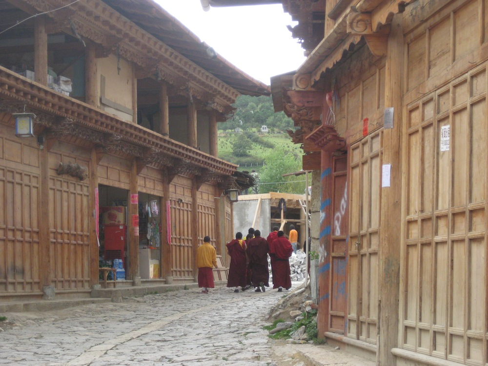 "Young monks stroll down a street of new ""traditional"" houses in Old Town"