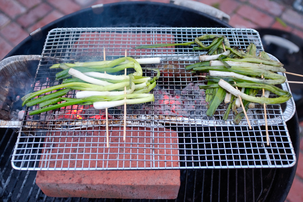Scallions cooking over very hot coals (on the left) and being kept warm over older coals (on the right)