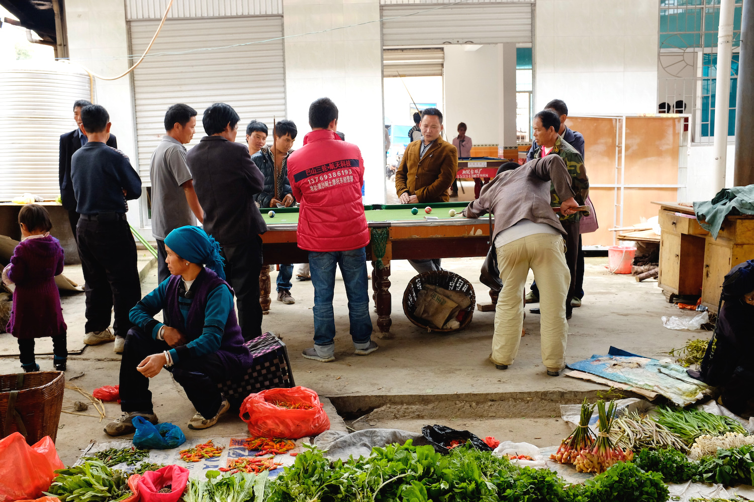 The men relax while the women sell vegetables