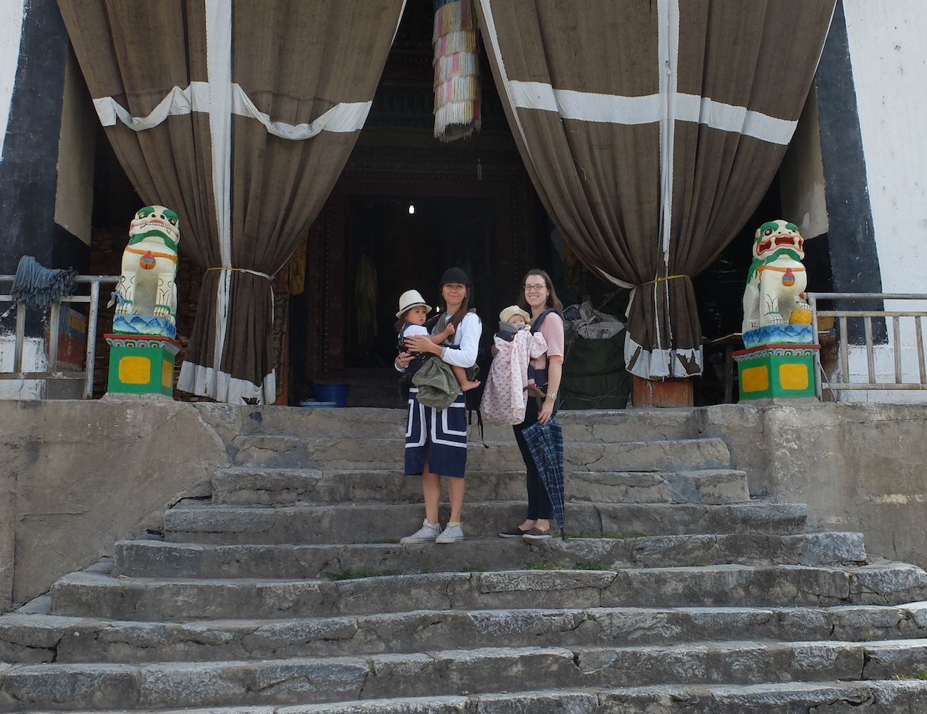 Two moms and two babies on the steps of Hongpo Monastery