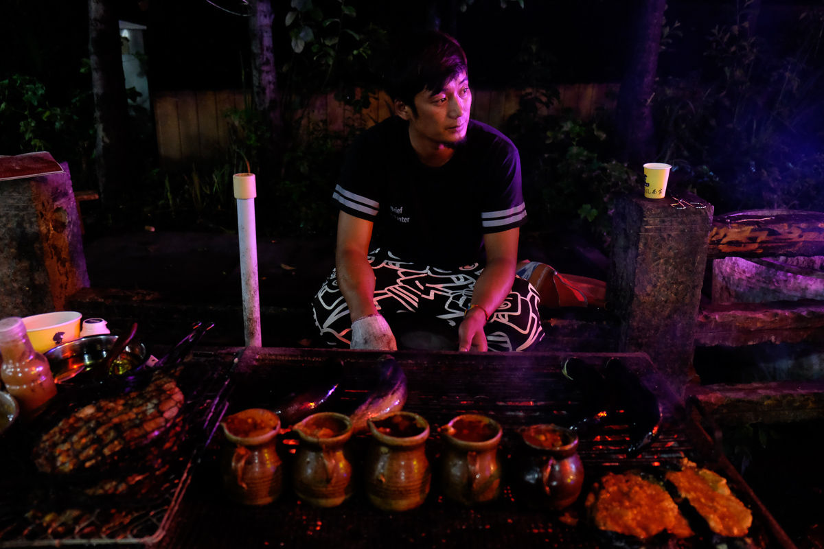 A cook prepares grilled fish and eggplant and little pots of pigs brain at a street-side barbecue restaurant